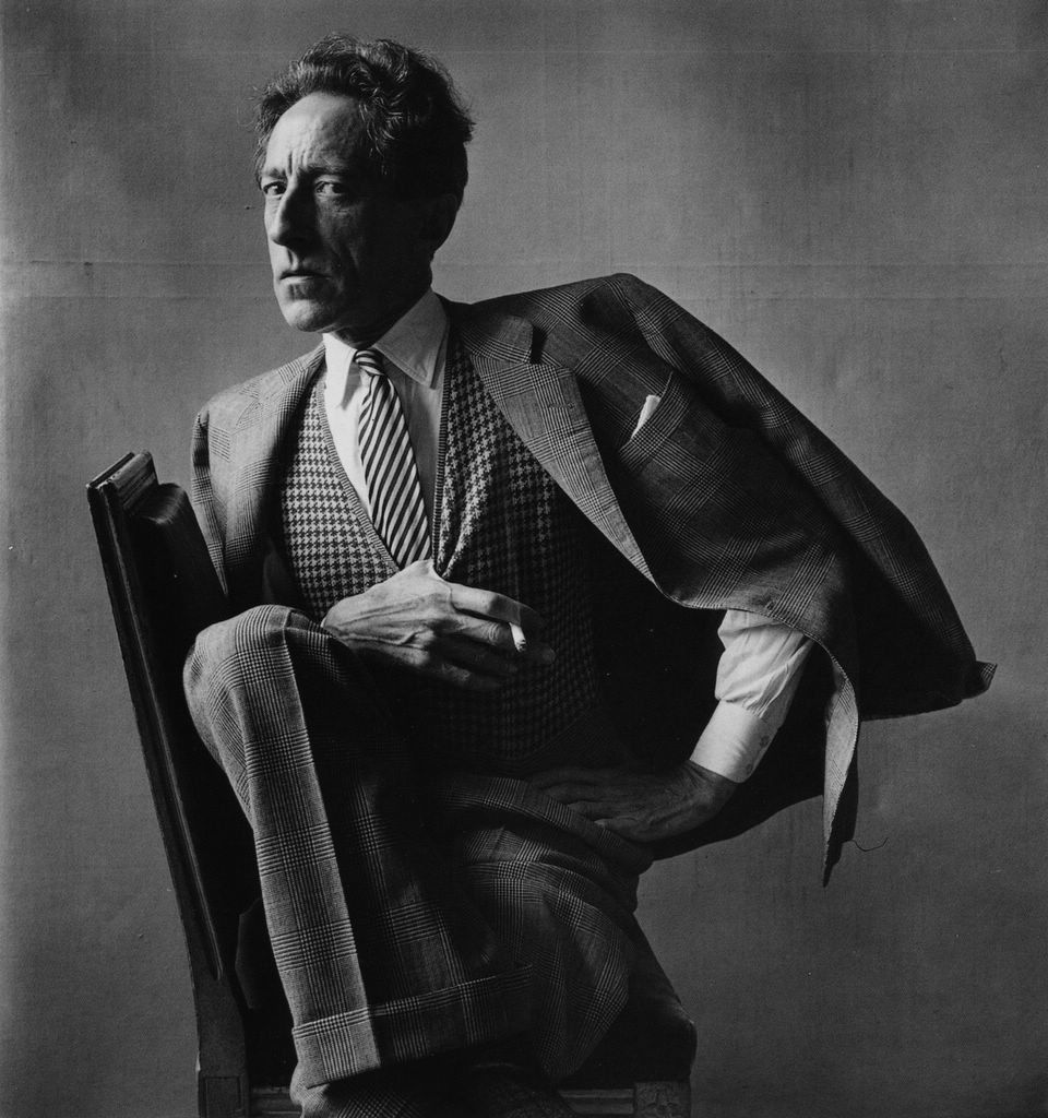 """Jean Cocteau photographed by Irving Penn 1948 Paris.    """"Each thread of Cocteau's tie, vest, and suit is etched in light and shadow; the patterns and the texture pop out in vivid, tactile detail.  The drape of his coat over an extended arm adds drama and balance to the composition. There is an air of flamboyance about him, until you look at his face.  His dead-serious expression registers the fierce intelligence of a keen observer."""" –Philip Gefter"""