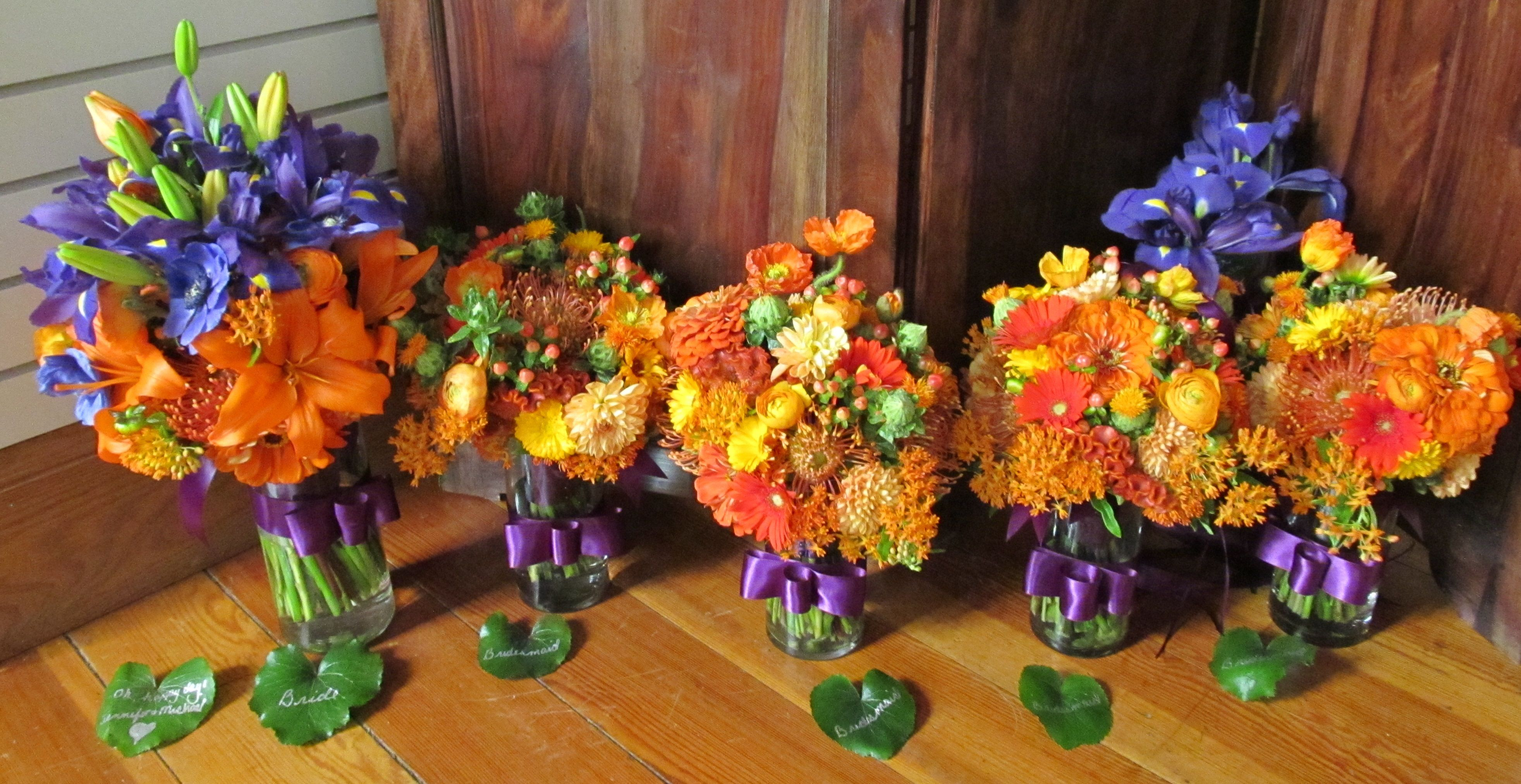 Bouquets of orange lilies, purple iris, purple anemone, orange ranunculus, aslepias, zinnia, pincushion protea, fan celosia, gerbera daisies and calendula by The Peony & The Peacock