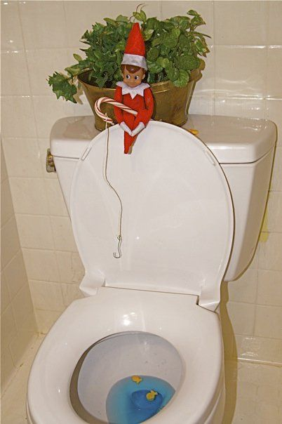 elf fishing for gold fish in the toilet bowl with a candy cane pole... LOL