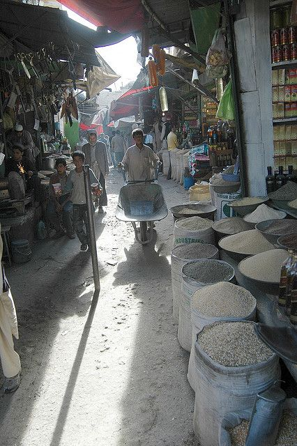 A boy sells brooms at a roadside stall in Mazar-i-Sharif
