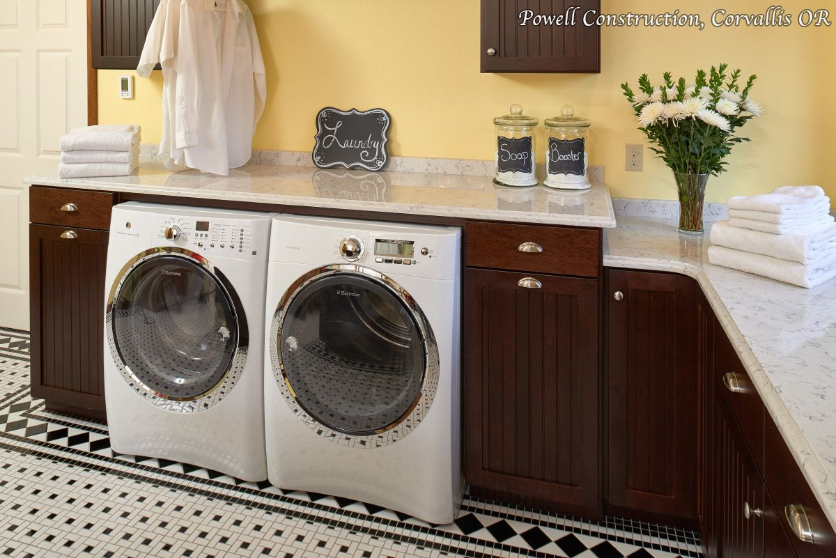 A Sunny Yellow Laundry Room With Side By Washer Dryer Black And White Tile Dark Stained Maple Cabinets Quartz Countertops