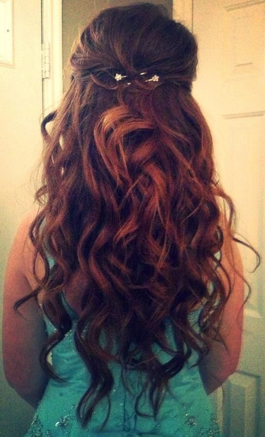 Prom hair. Thick messy dark brown curls with auburn strands, pinned half up with a small flower clip.
