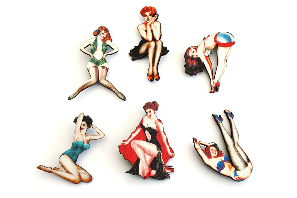Cheeky wooden pin up models strike they're favourite pose on a silver plated brooch back