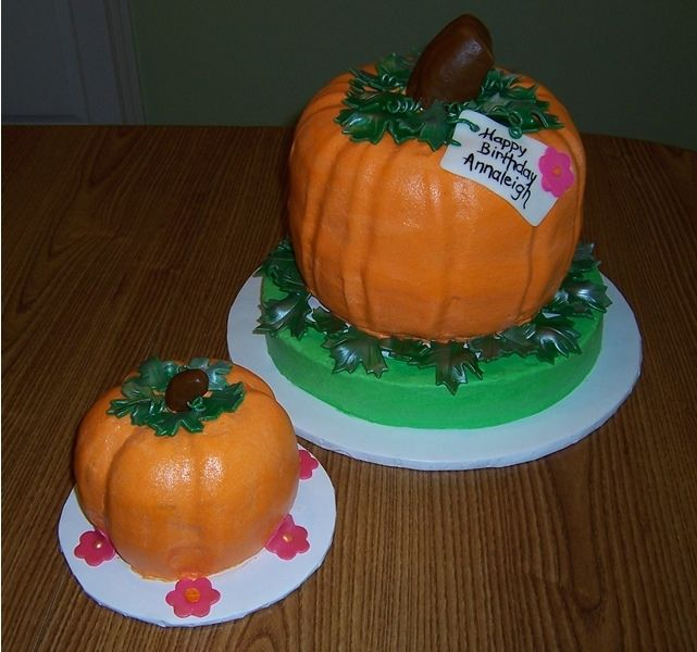 Pumpkin shaped birthday cake with mini pumpkin smash cake. Large made with bundt cake method, and small one was 6 in layer, carved. Fondant accents. #pumpkinshapedcake