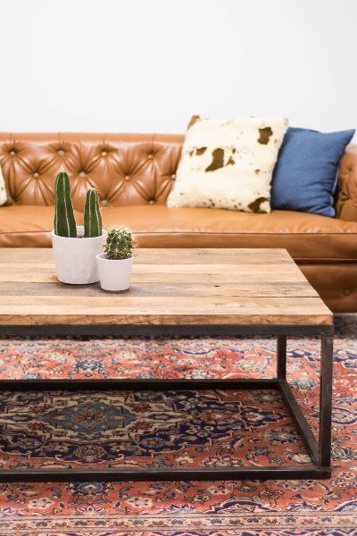 lounge brown leather tufted sofa faux cowhide pillows demin throw industrial metal and wood coffee table pink blue persian rug also our collection of vintage modern rental furnishings living