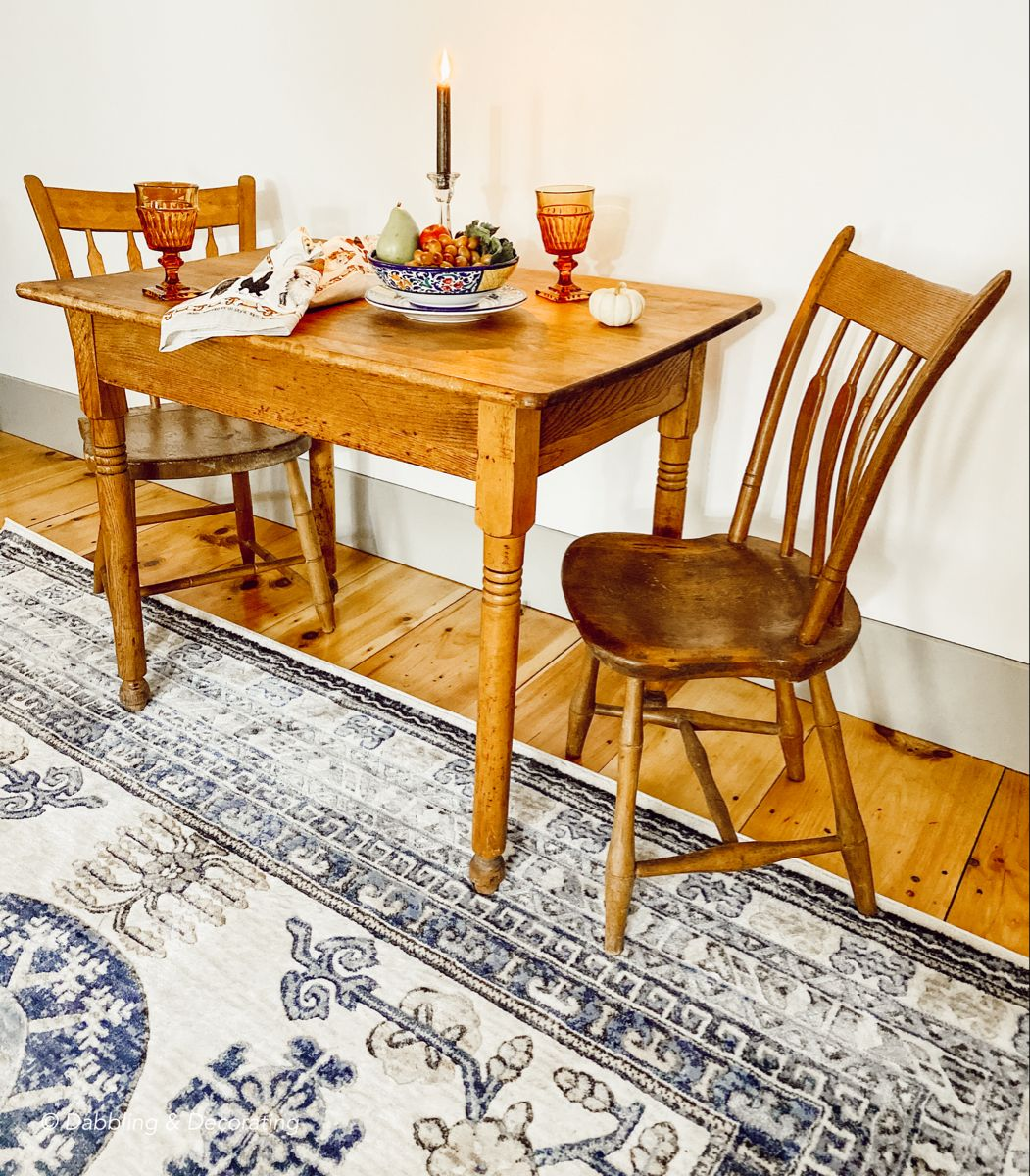 A small antique table for two in our coastal Maine home living room for fireside dining, coffee, beverage table, and so much more! #table #tableandchairs #antiquetable #vintage #vintagedecor #vintagehomedecor #vintagestyle #vintageaesthetic #vintagehome
