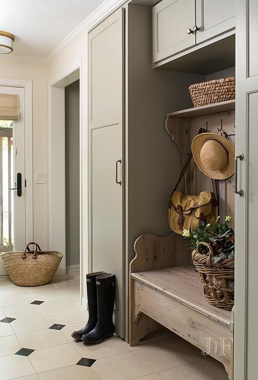 Cottage Mudroom Features Gray Green Cabinets Flanking A Freestanding Bench With Coat Hooks