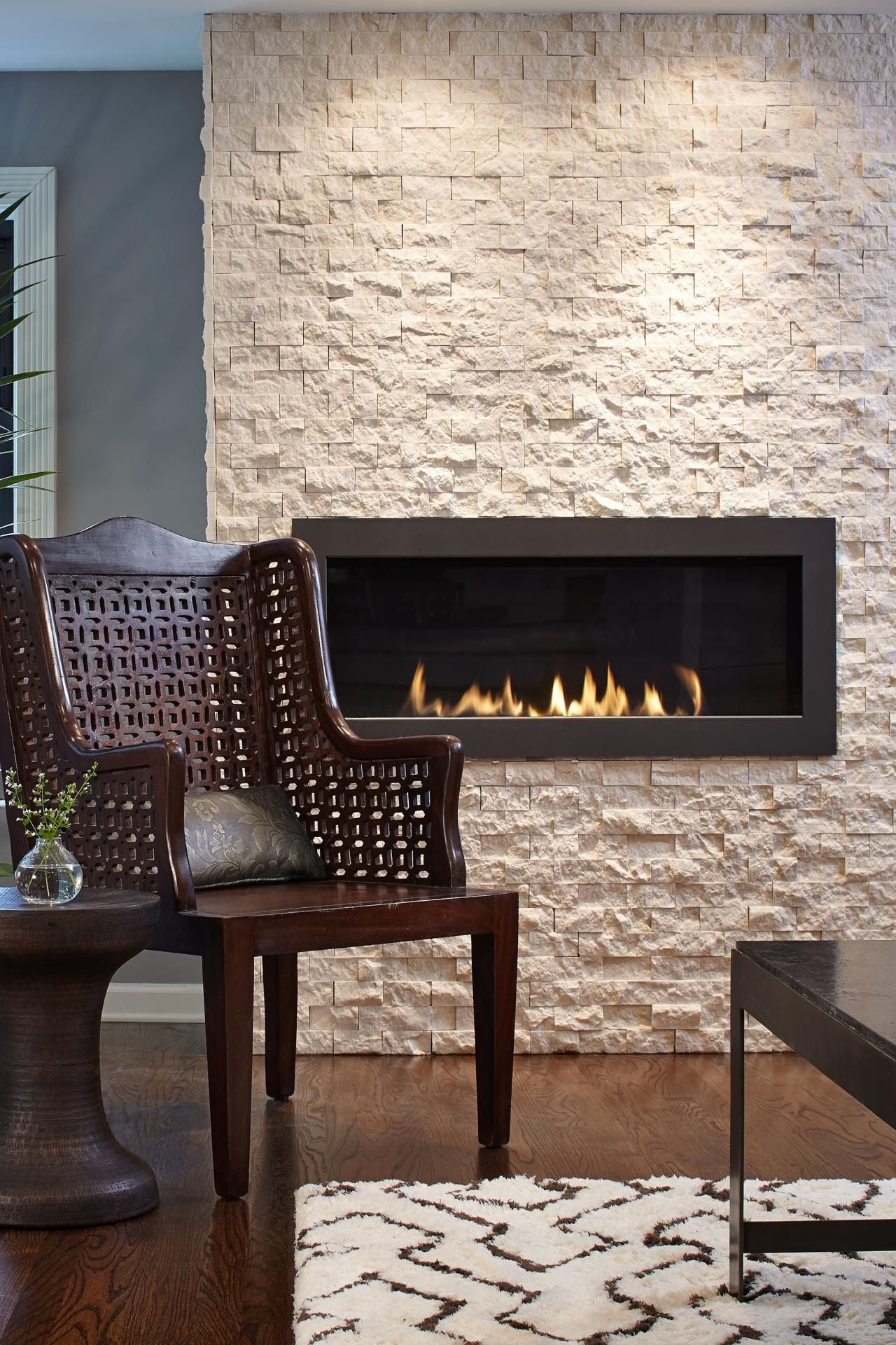 white limestone wall with fireplace and chair hgtv fireplaces