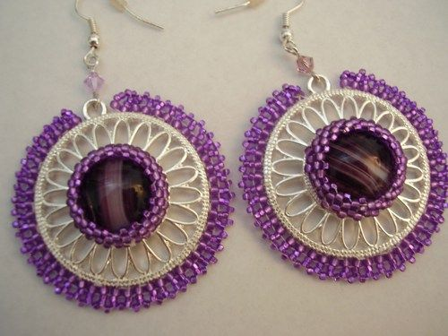 If you love drama with lots of style in your jewelry, these earrings are just the thing to wear any time of the year. The Amethyst glass cabochon centered in the silver metal filigree is surrounded by