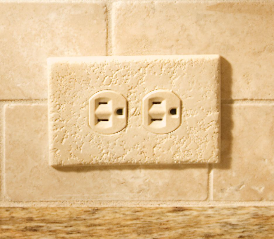 This painted outlet cover blends into the stone backsplash. This ...