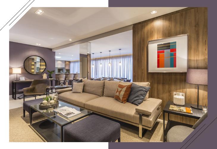 O mobiliário de linhas retas traz sofisticação ao ambiente, que apresenta o acabamento amadeirado Laminato Larice no painel atrás do sofá. Aparadores, pufes e mesas laterais conferem um ar leve e dinâmico ao espaço.
