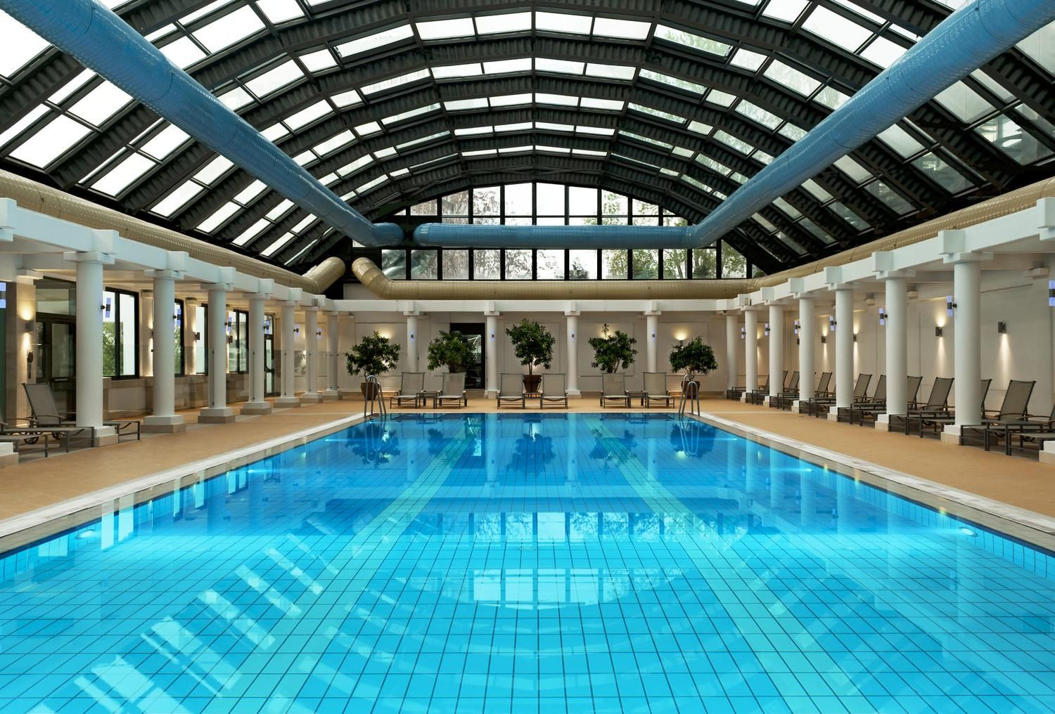 Luxurious Indoor Pool Design With Huge Rectangle Shaped Pool And Lovely Beach Chairs And