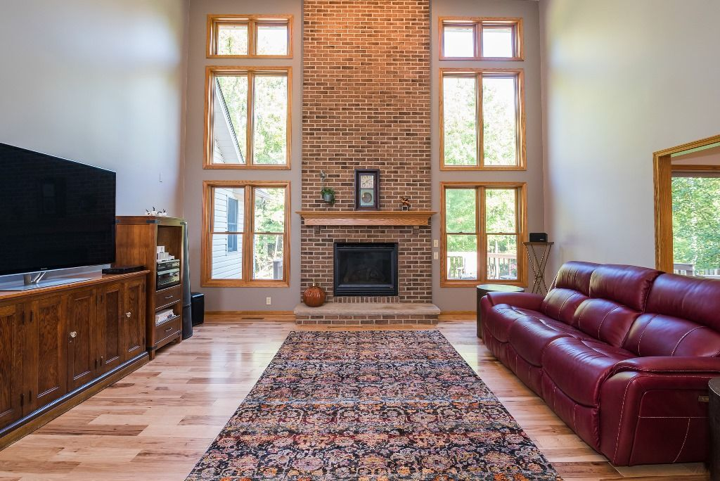 The Two Story Great Room Offers A Floor To Ceiling Brick Front Fireplace Flanked By Floor To Ceiling Windo Great Rooms Ceiling Windows Floor To Ceiling Windows