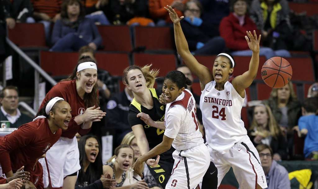 Oregon's Sabrina Ionescu, center, gets off a pass as Stanford's Briana Roberson and Erica McCall (24) defend, in front of the Stanford bench during the first half of an NCAA college basketball game in the Pac-12 tournament, Saturday, March 4, 2017, in Seattle. (AP Photo/Elaine Thompson) Photo: Elaine Thompson, AP