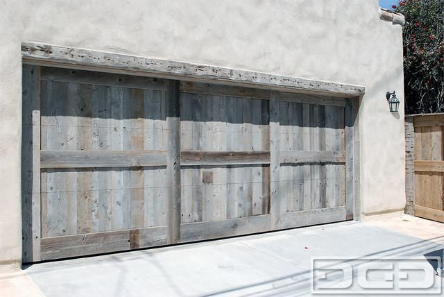 Custom made reclaimed barn wood garage door in a rustic for Rustic wood garage doors