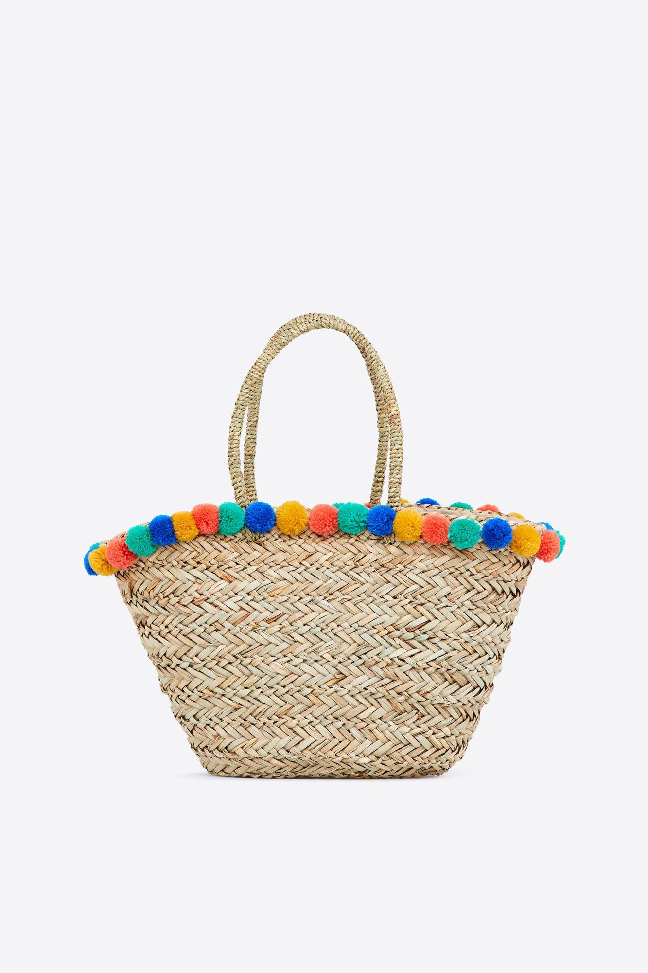 f424b4ba85b Bolso estilo canasto de playa con borlas decorativas. El complemento  perfecto para los días de playa.