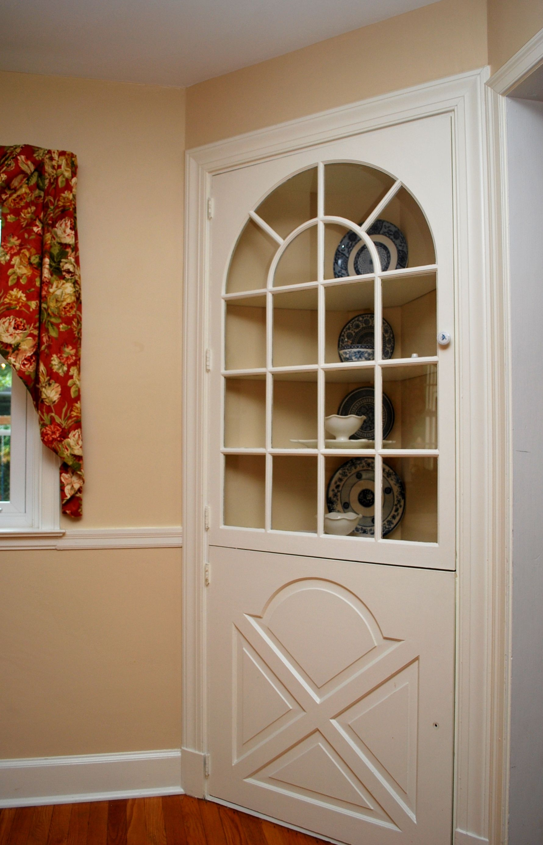 another builtin corner cabinet with an arched window and more detailed cabinet door