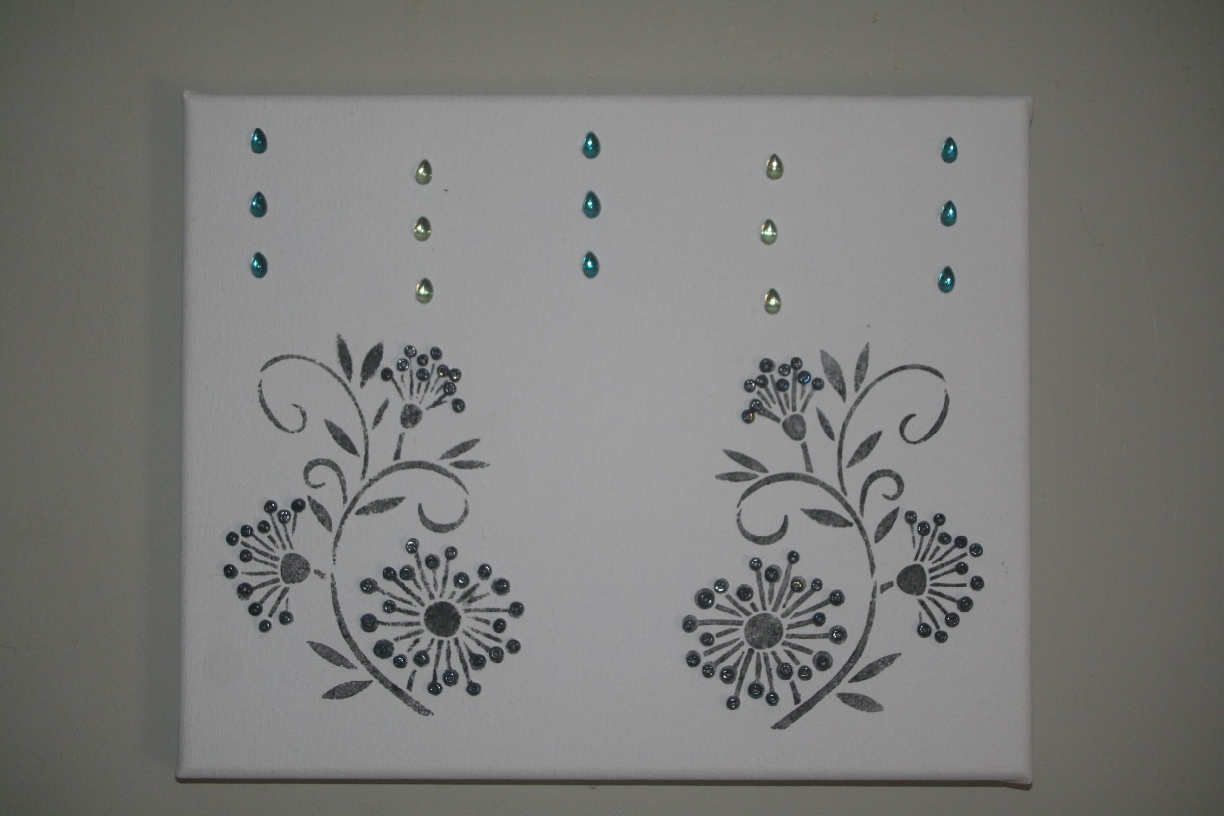 "stencil flower design in charcoal ink on plain canvas, added jewel ""rain"" drops and small beads as flower petals."