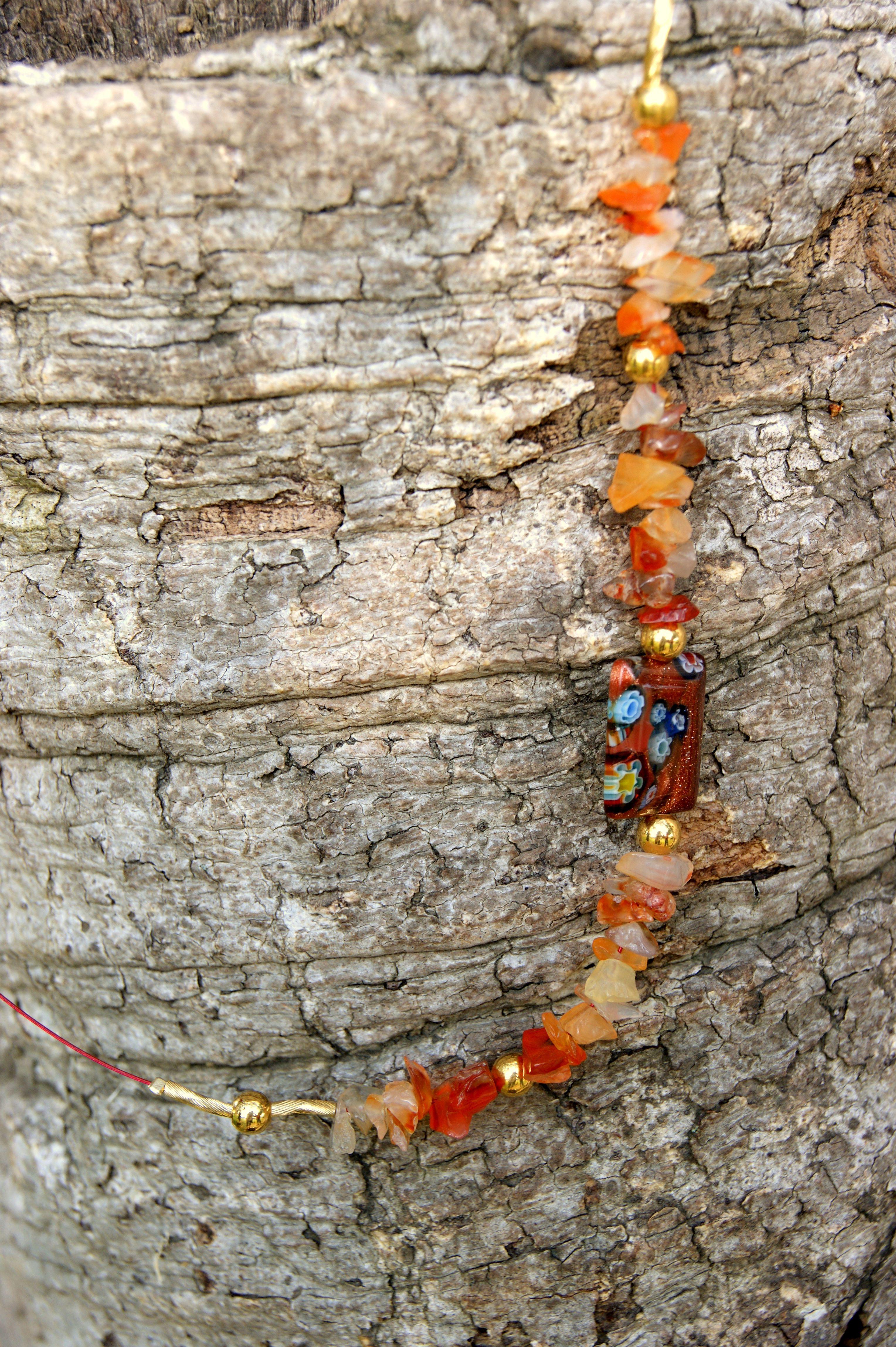 Collar de plata dorada con piedras naranja y dije de murano en mismo tonos, engarzados en hilo plastificado color naranja