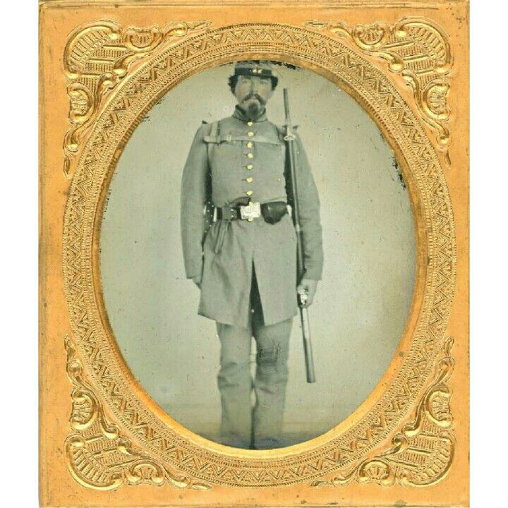 A REBEL DOUBLE ARMED WEARING A KNAPSACK, 1/6th plate ambrotype in a full leather case. This Rebel stands posing in regulation uniform with kepi showing the leather straps of a knapsack on his back. In his belt is a Whitney revolver and to his left he holds a Model 1841 Mississippi 54. Caliber musket. He also has a leather cap box on his belt. The image is crystal clear. The image is free from any marks or damage. His buttons are tinted gold and his belt buckle silver, which is unusual. He…