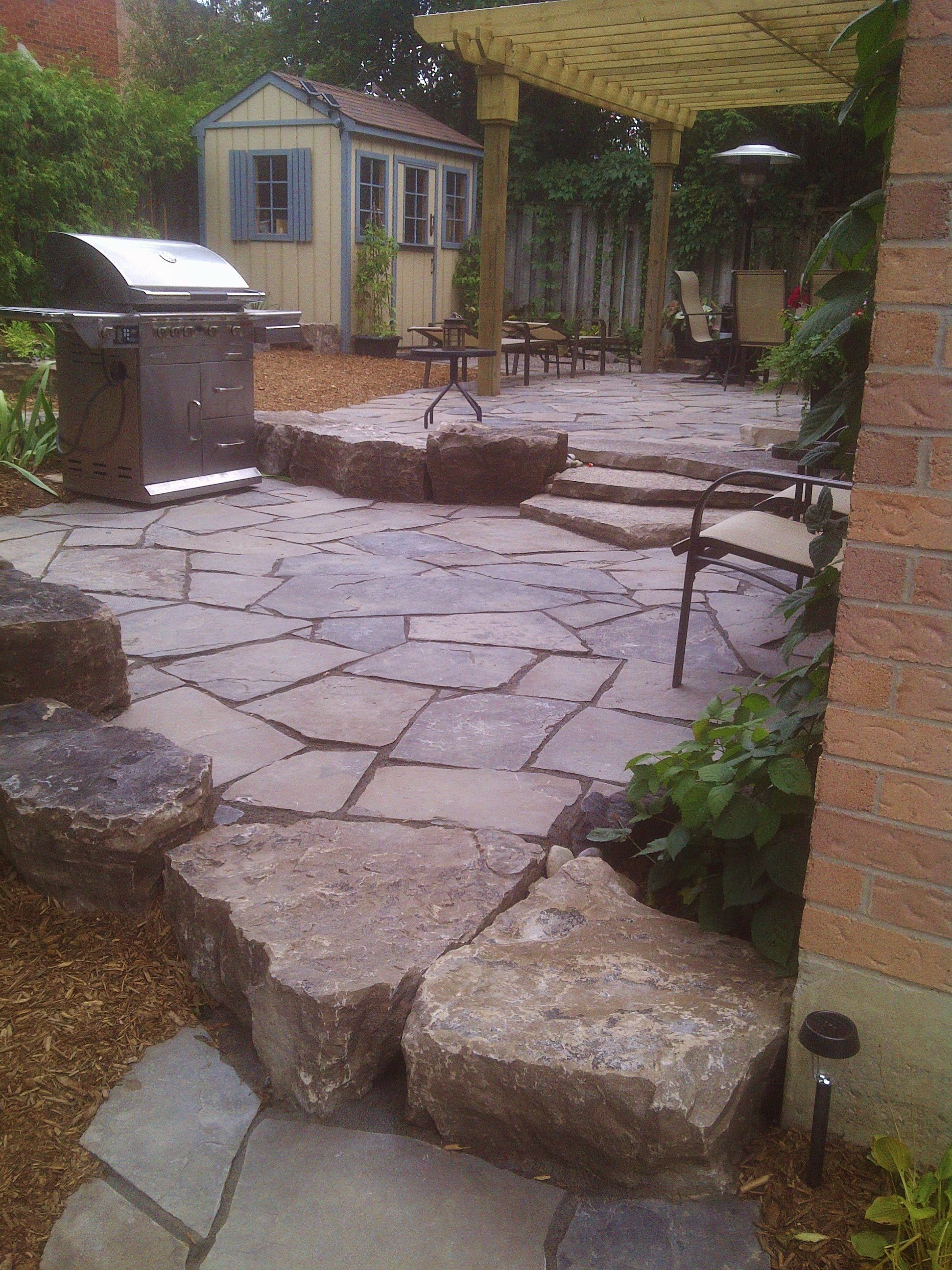 2 tiered random flagstone patio with armour stone walls and steps