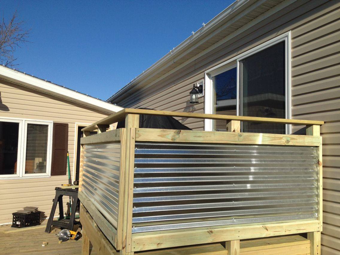 Corrigated Metal Roofing used on its side as a panel for deck railing. Turned out excellent!