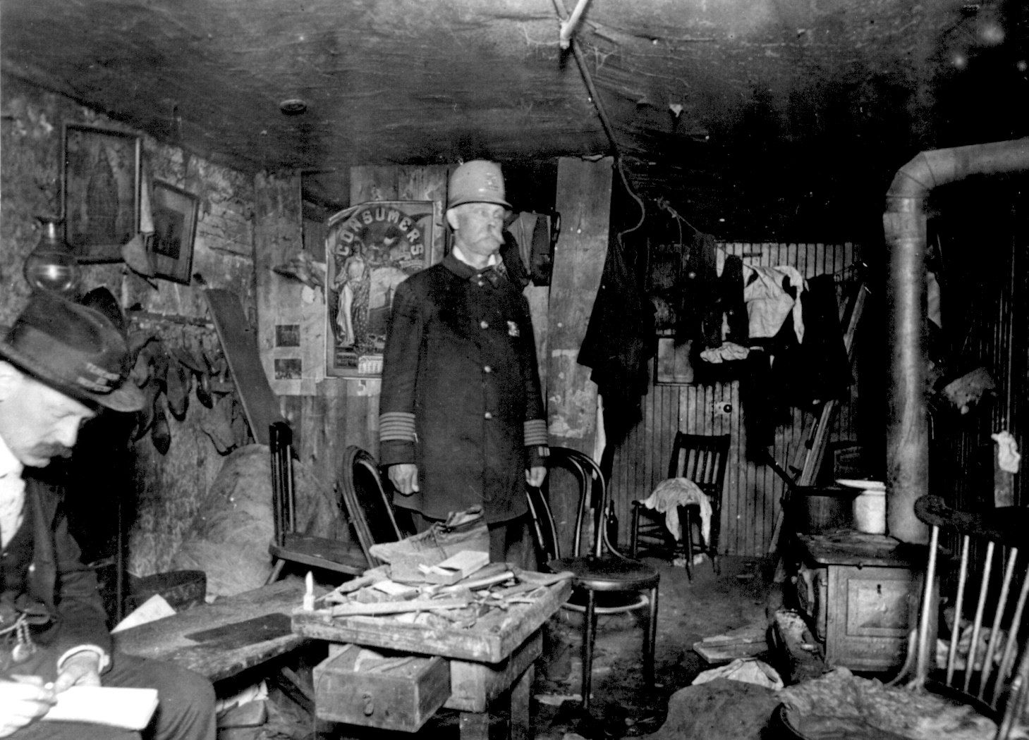 two officials of the new york city tenement house department two officials of the new york city tenement house department inspect a cluttered basement living room