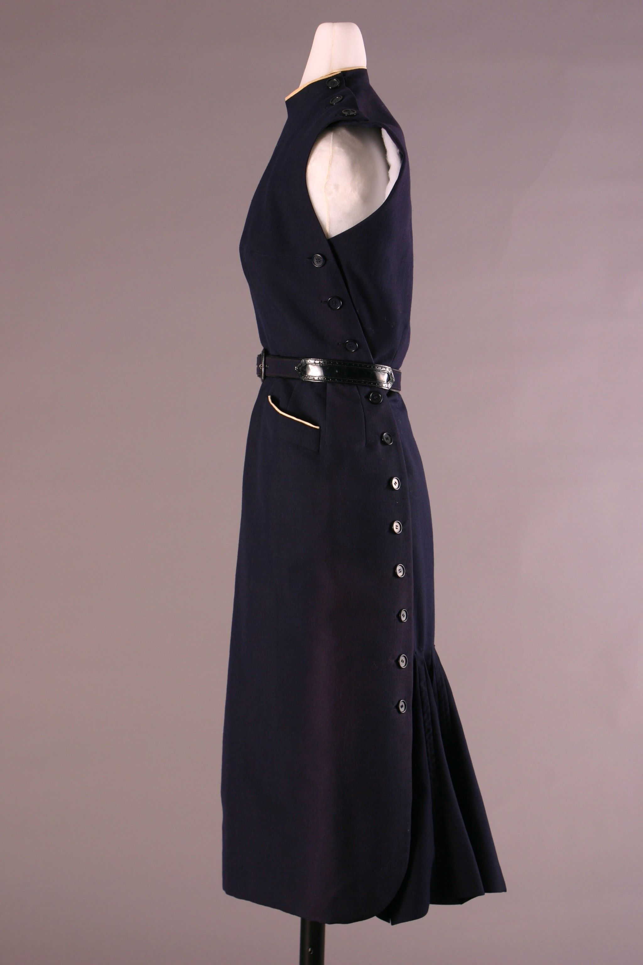 Christian Dior Dress - 1947.  Sleeveless sheath dress in navy blue wool/silk or wool/mohair blend. Composed of two panels, front and back, buttoned together at shoulder and along sides. Back panel pleated from knee-level to hem.