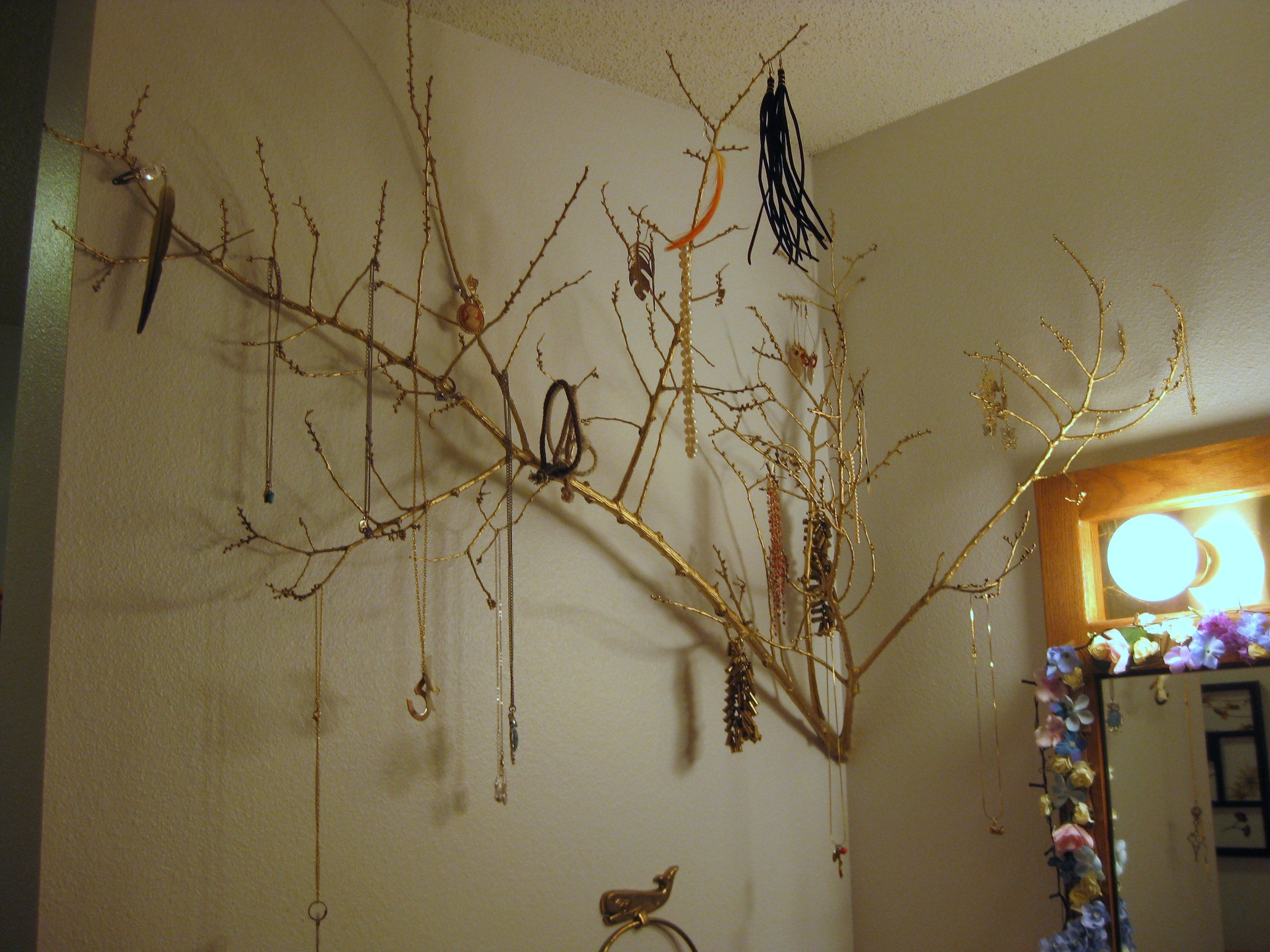 Jewelry tree! Made with spray painted tree branches, attached to the wall with screws that have fishing line tied around the head and wrapped around the branch.