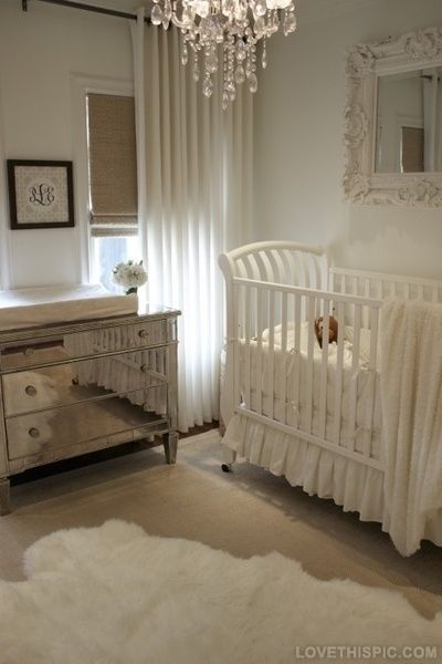 Ultra Glam A White Nursery Baby Room With White Sheepskin Rug Mirrored Dresser Change Table Chandelier And White Crib