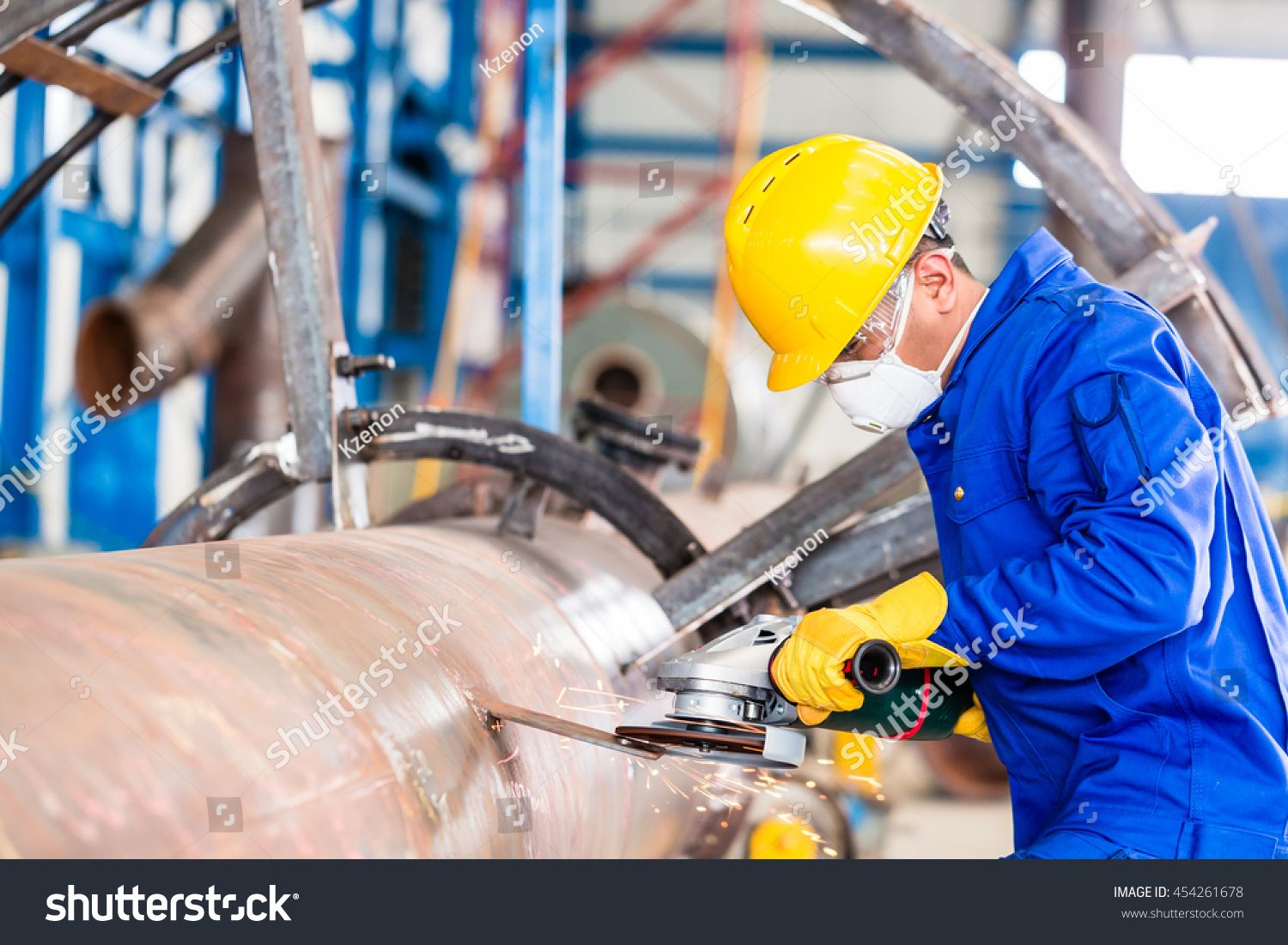 Industrial worker in manufacturing plant grinding to
