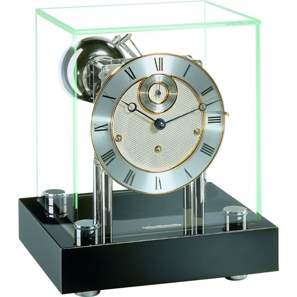 Inspired by the minimalist elegance of the cube, this clock will rank amongst the classics of its genre. The polished nickel plated Westminster movement is supported by heavy pillars mounted onto a black piano wooden base.