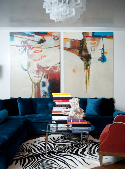 Room decor ideas a young living room full of color the white wall is hidding with two giant painting the velvet dark blue sofa gives life to the room