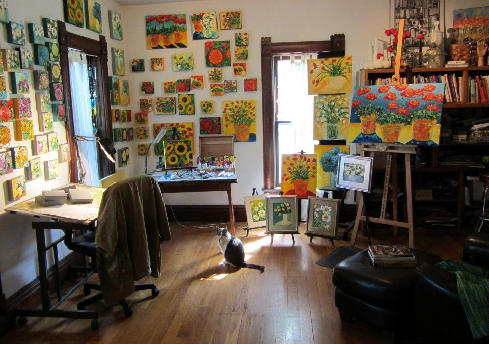 Home art studio, I love this...surrounded by paintings of flowers ...