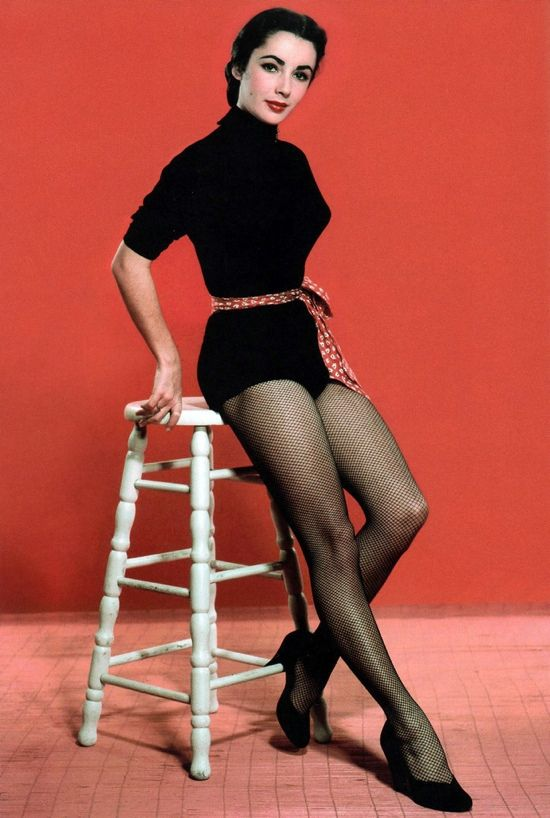 A young fresh-faced Liz Taylor posing for a pin up photo in fishnet tights