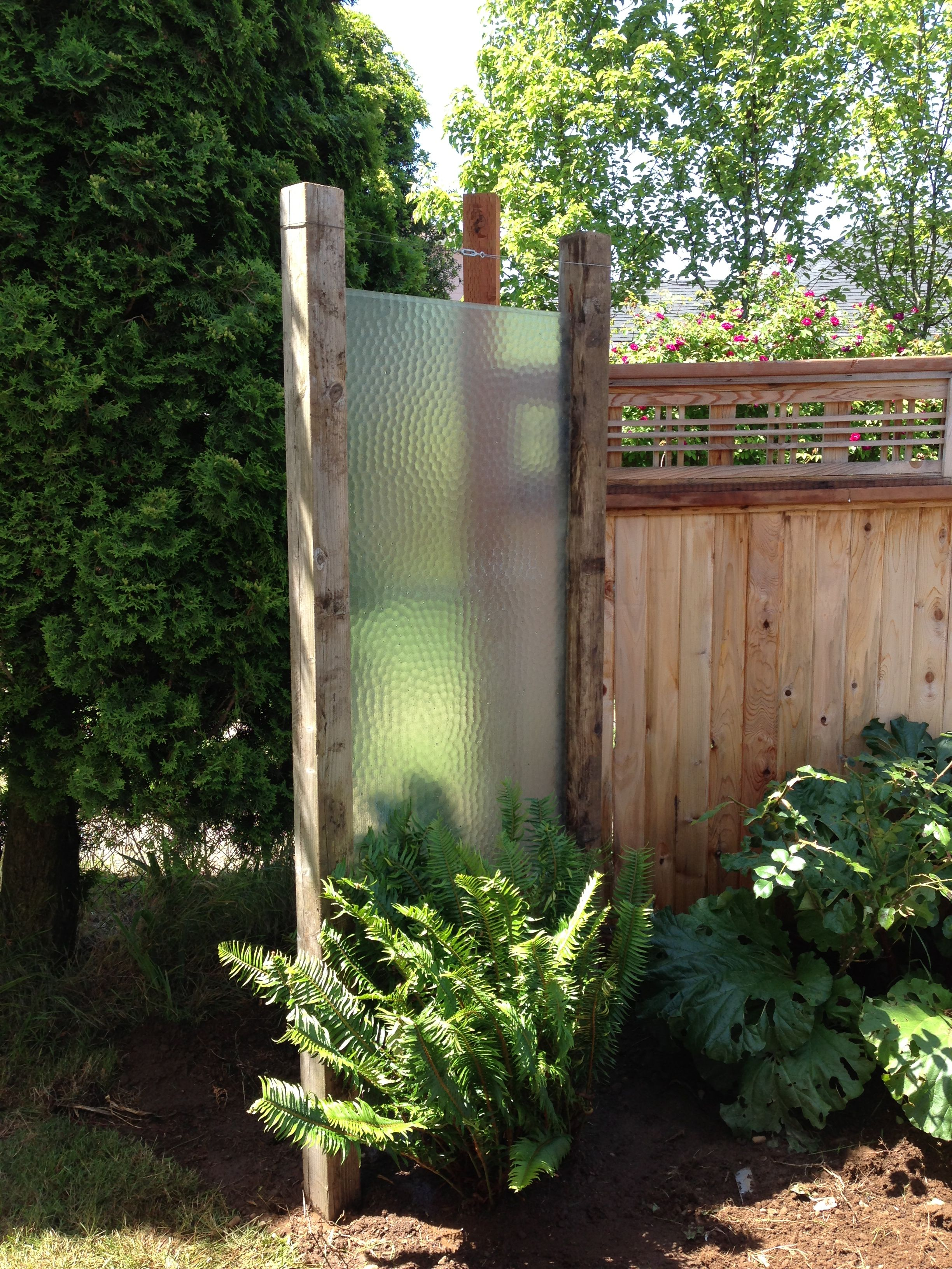 up cycled turned an old shower door into an outdoor privacy