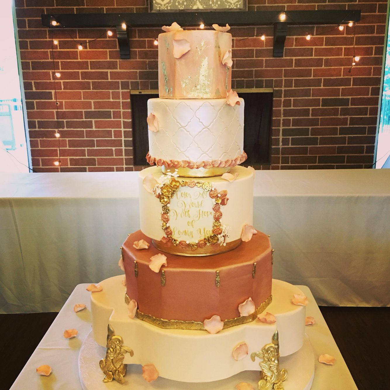 Stunning metallic rose gold, gold, and peach wedding cake -- floating on gold feet. Look at the detail in the tiny flower frame with the sweet sentiment.