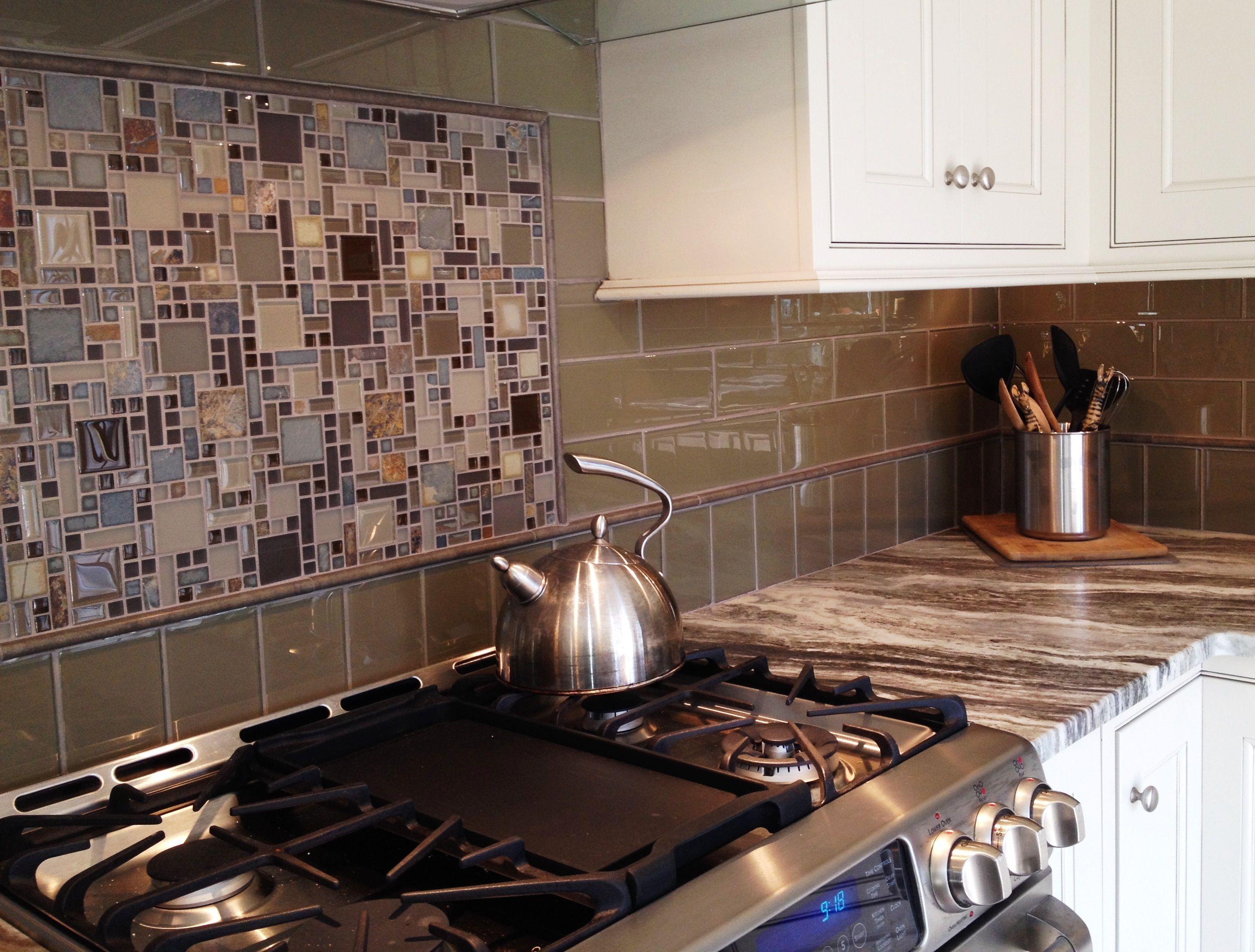 Glass tile backsplash with framed mosaic tile insert over the