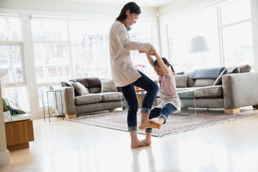 Daughter dancing on mothers feet in living room