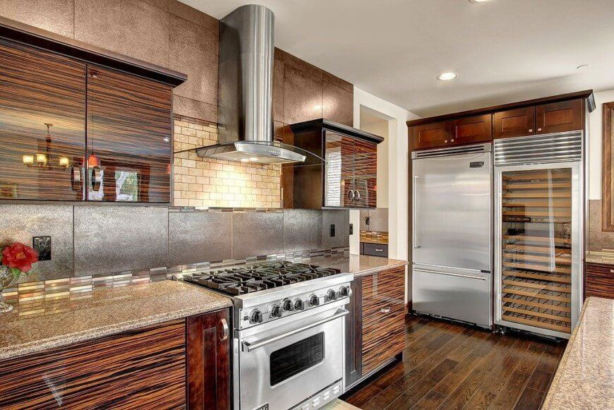 We love the sleek texture of the wood cabinetry in this kitchen, adding a glossy sheen to a space dominated by the contrast between natural wood and stainless steel. The countertops and backsplash provide an abundance of textural detail as well.