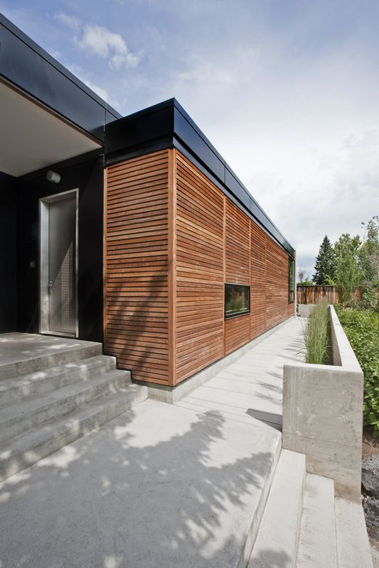 the front entrance of the hannon richards ferrier_webb residence located off of elbow drive, calgary / additional architectural interest is achieved through the directional use of materials and the contrast of warm wood with cool concrete/ residential / davignon martin architecture + interior design