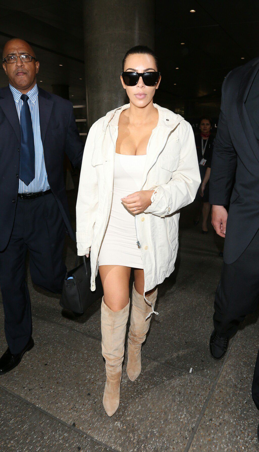 Kim Kardashian West in an oversize anorak, fitted minidress and Sergio Rossi boots.