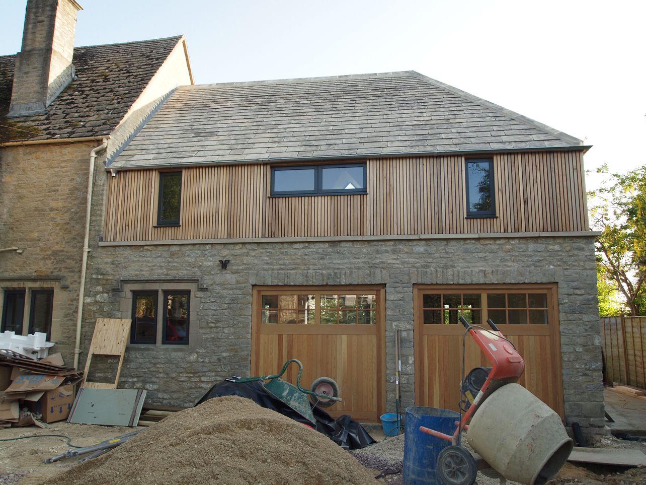 Vertical cedar cladding on an over garage bedroom for Cedar clad garage doors