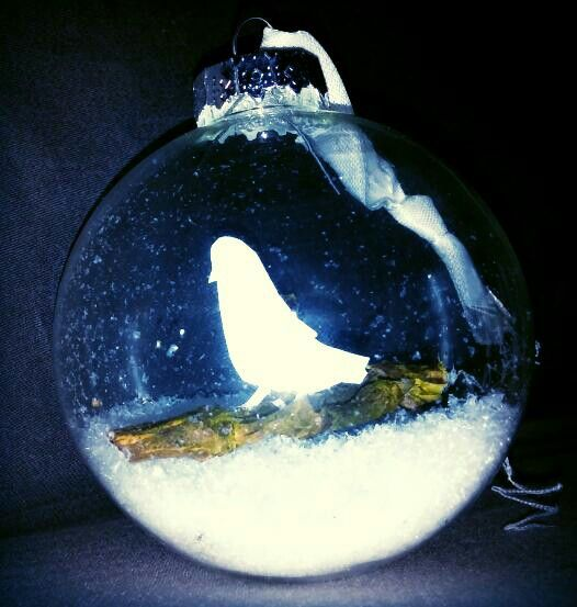Kerstbal van glas met vogeltje van papier op tak in sneeuw made by hieke