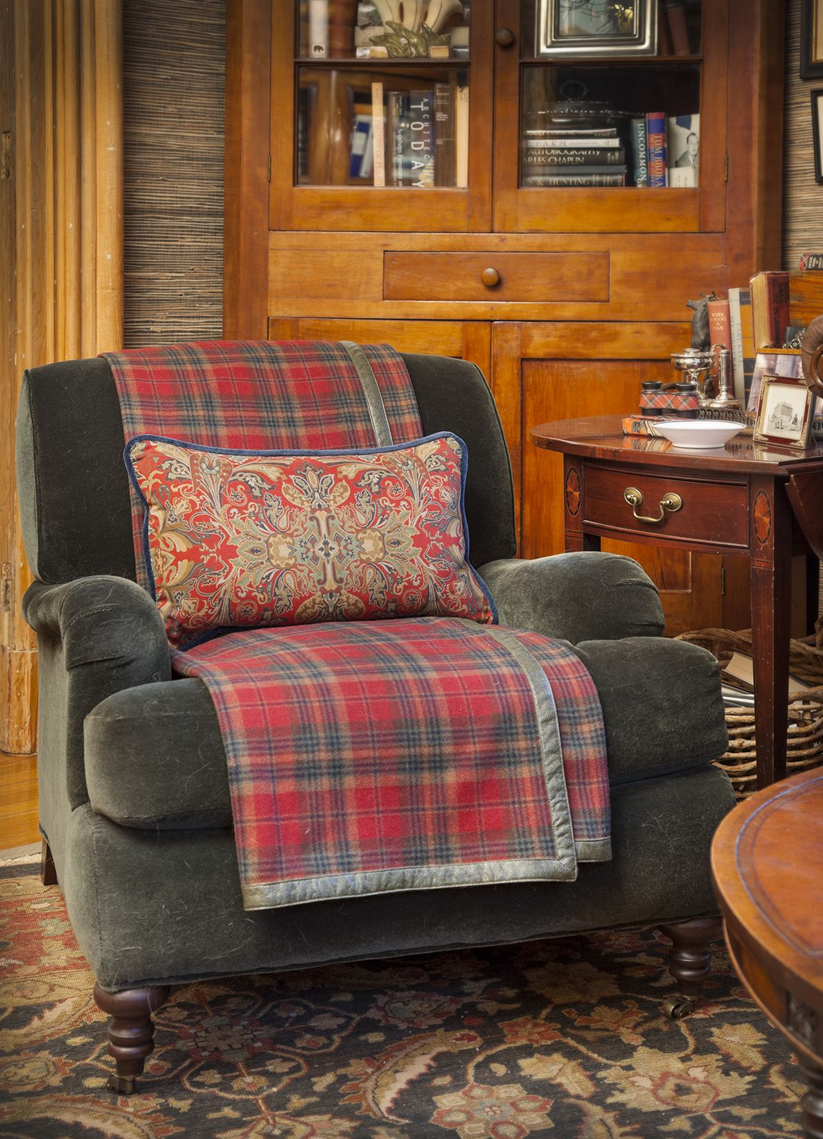 Green Chair With Plaid Throw Blanked And Paisley Pillow