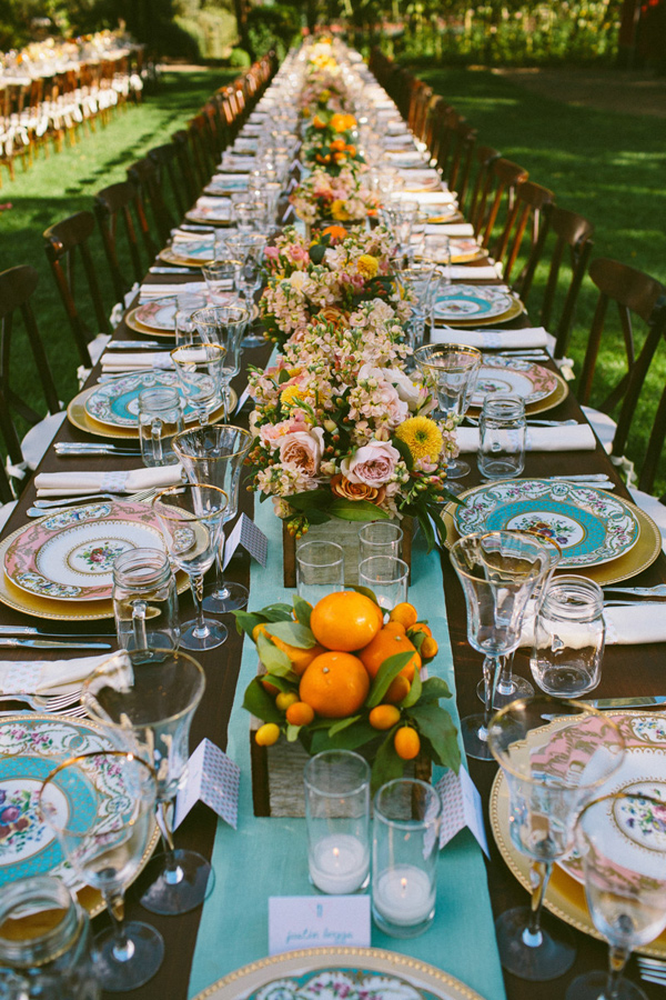 Colorful flowers and fruits centerpieces. Vintage china, candles ...
